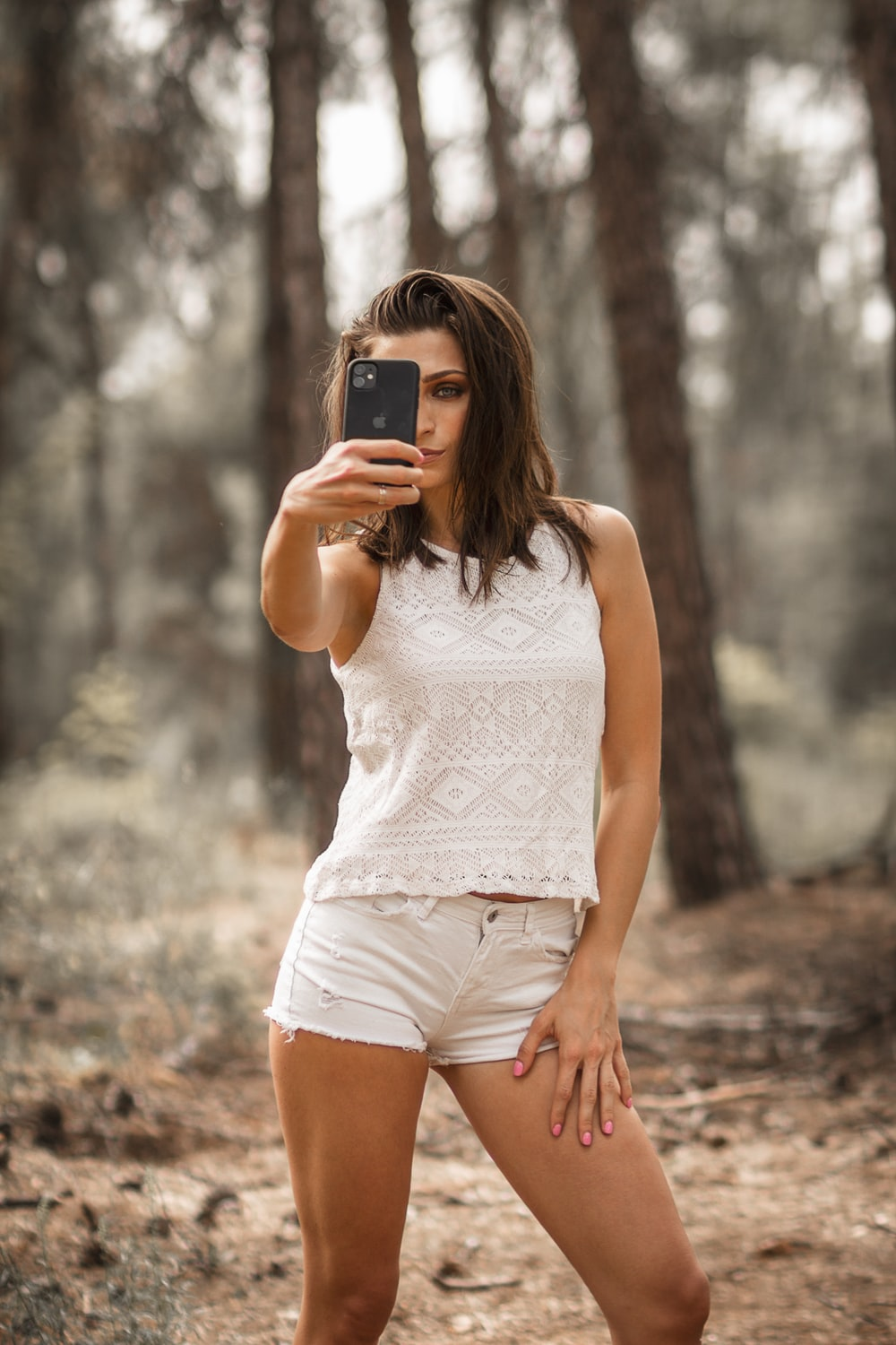 woman in white tank top holding black smartphone