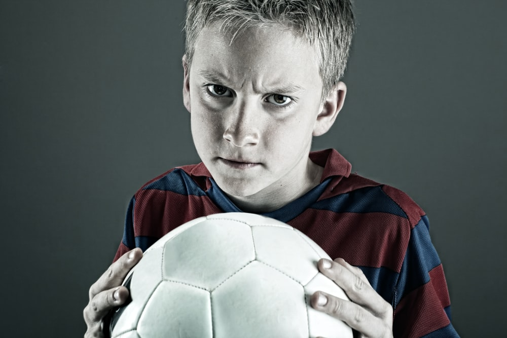 boy in blue and red jersey shirt holding white soccer ball