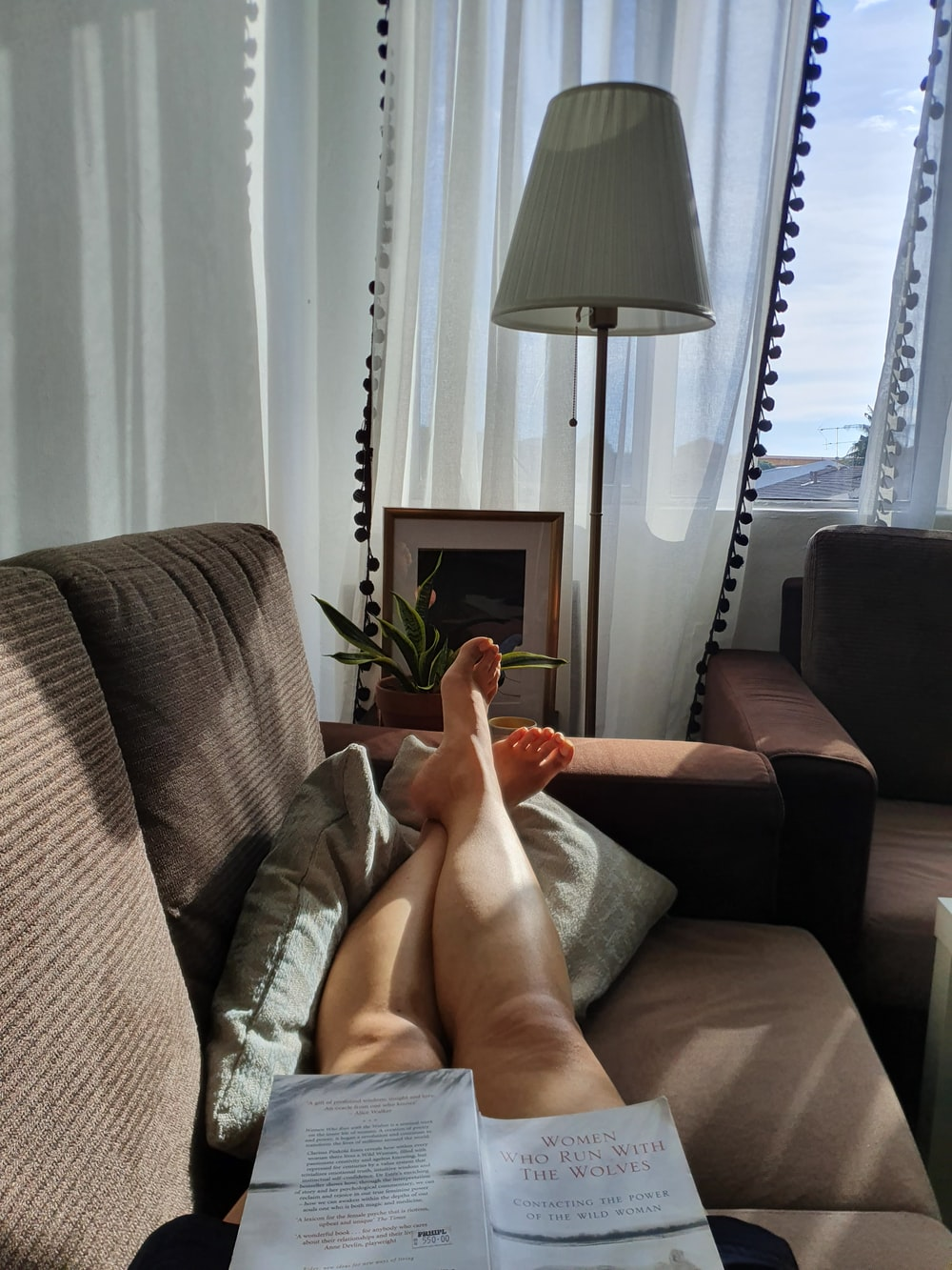 person lying on sofa near table lamp