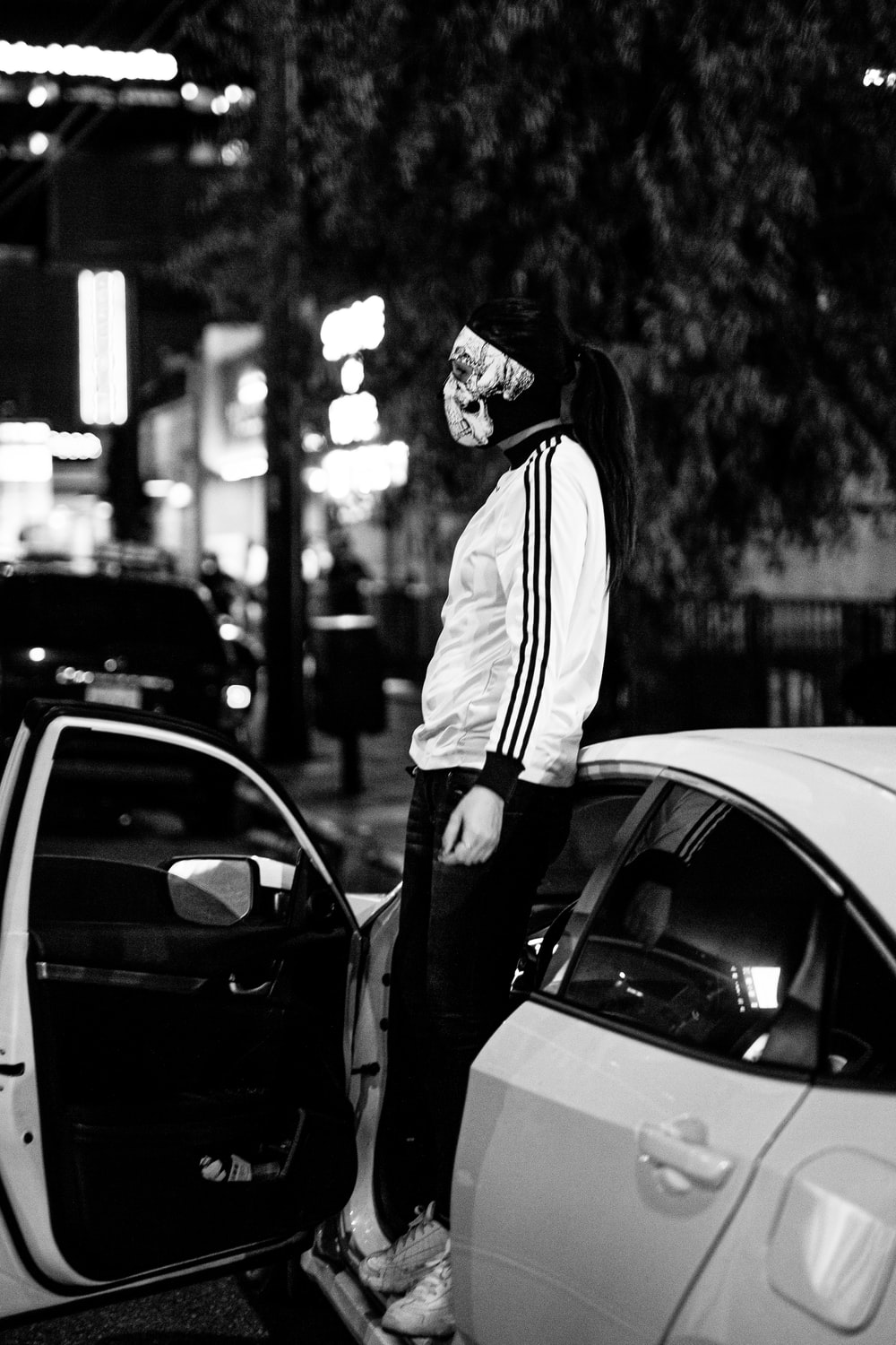 man in hoodie standing beside car in grayscale photography