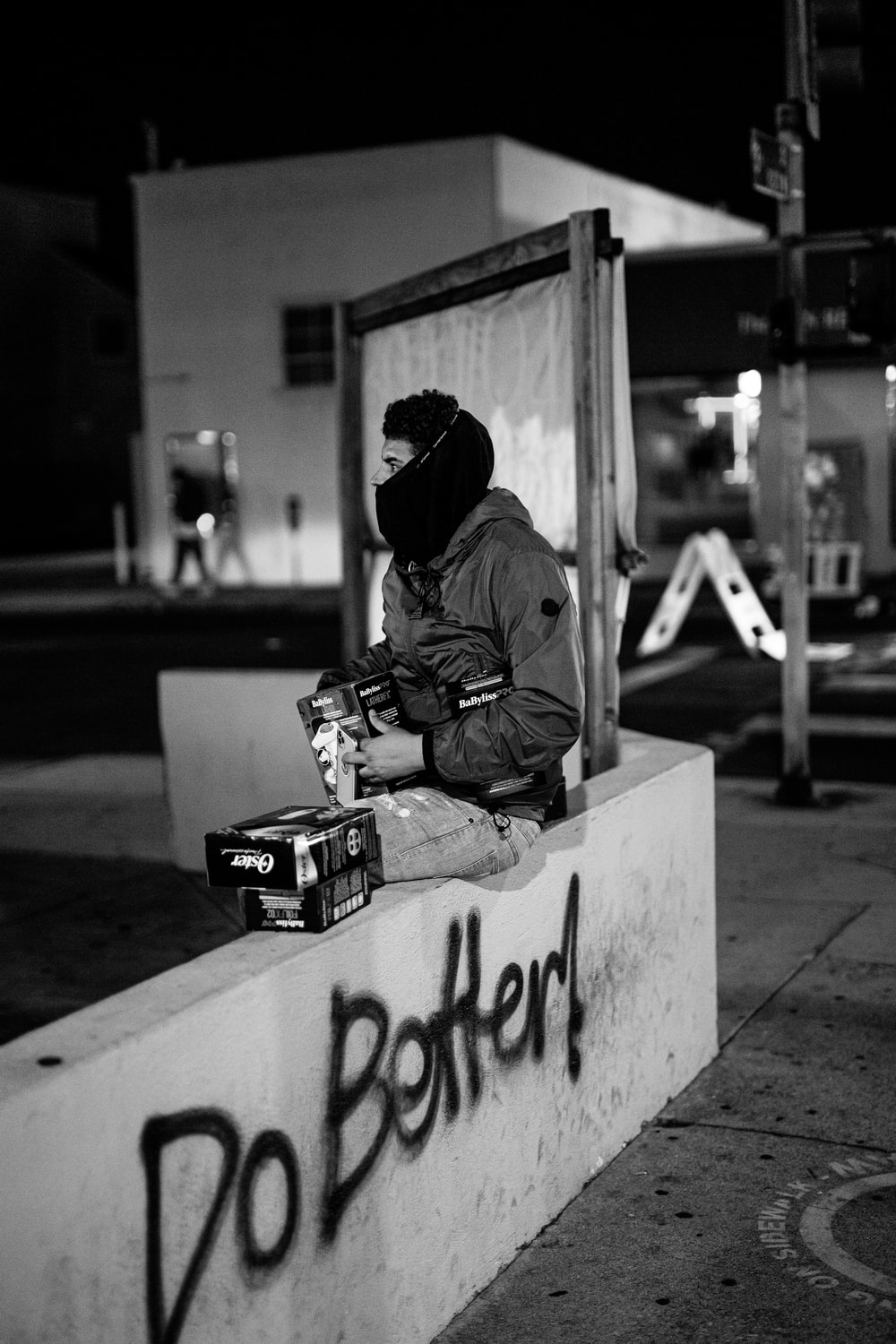 man in brown jacket and black knit cap sitting on concrete bench