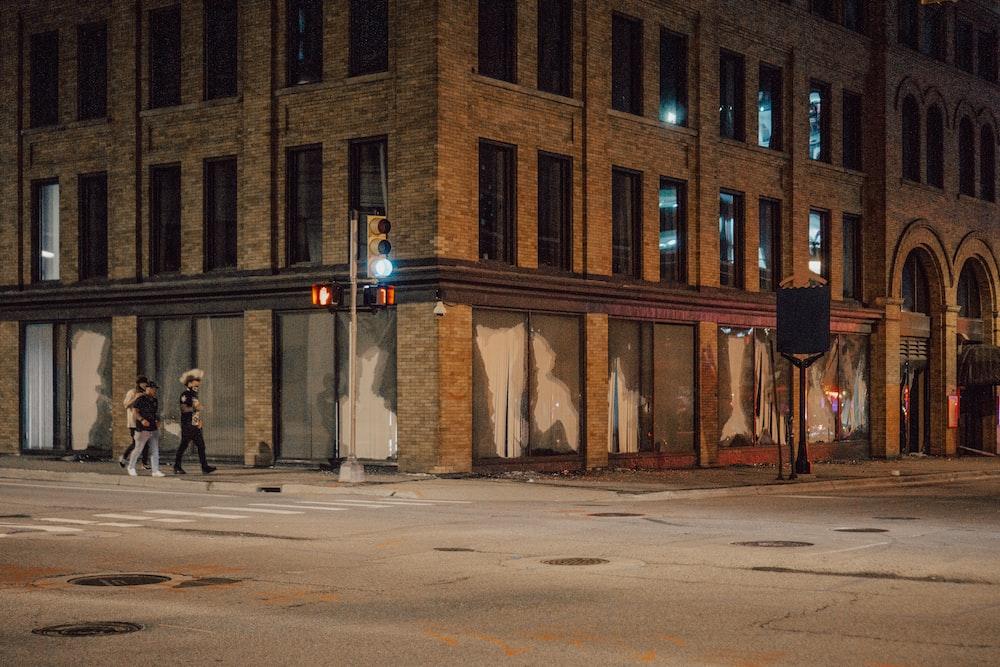 people walking on sidewalk near brown concrete building during nighttime