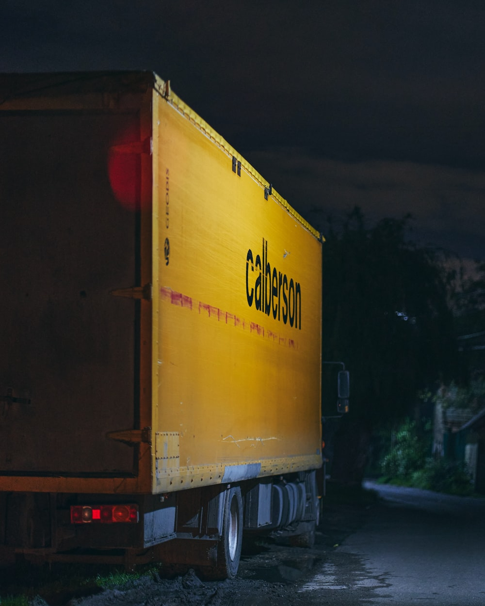 yellow and red box truck on road during night time