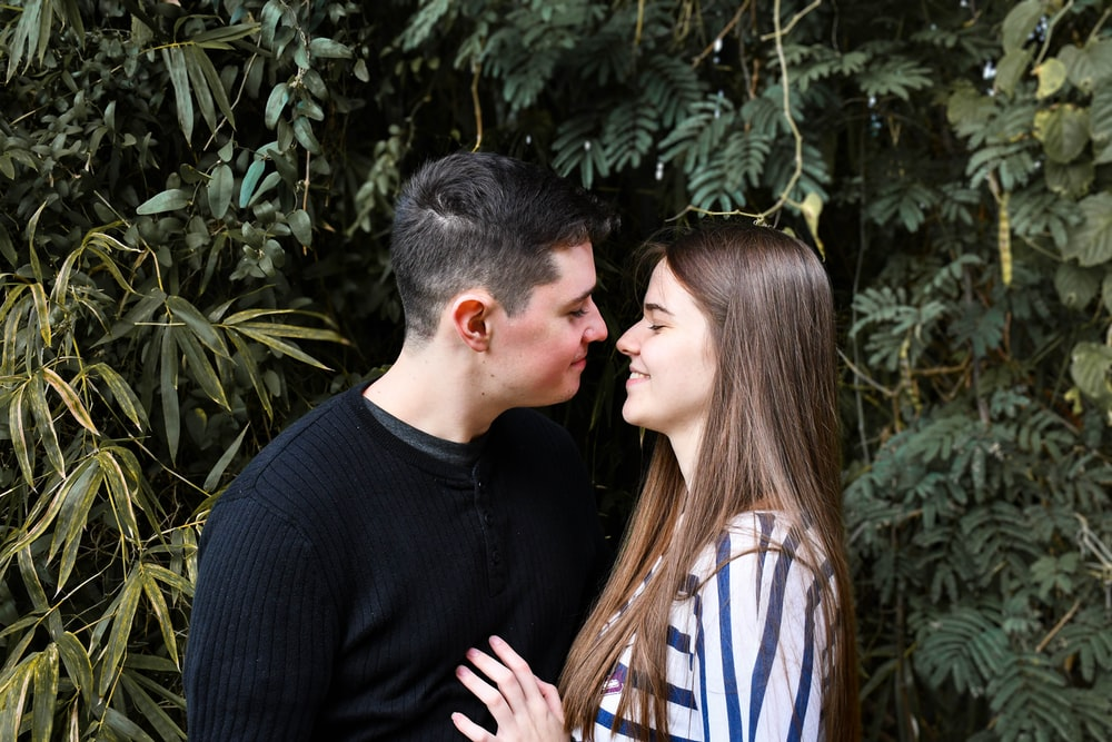 man in black sweater kissing woman in white and blue stripe shirt