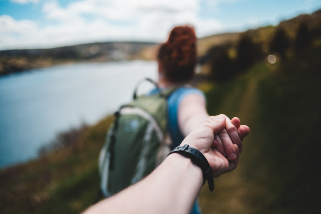 Person In Black Watch Holding Womans Hand - unsplash