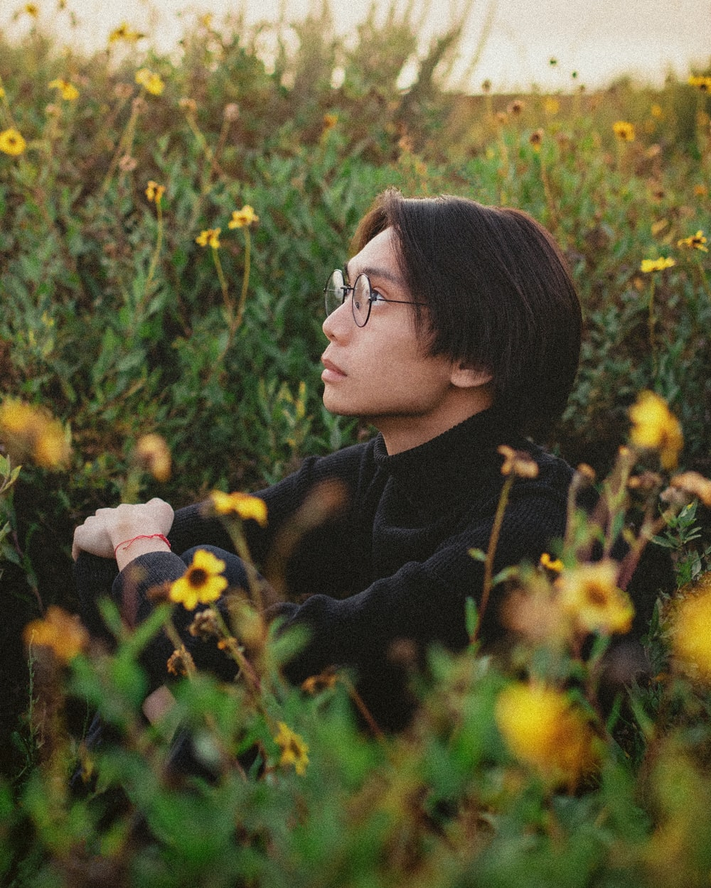 woman in black jacket wearing black framed eyeglasses sitting on yellow flower field during daytime