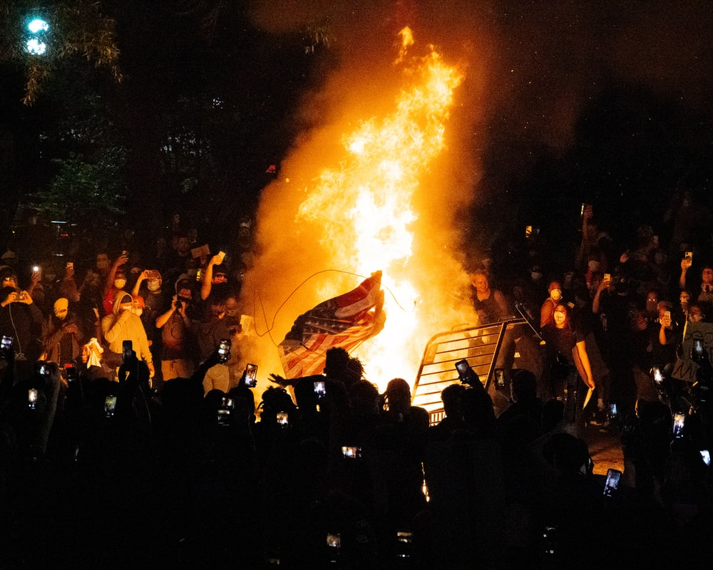 people gathering in front of bonfire during night time