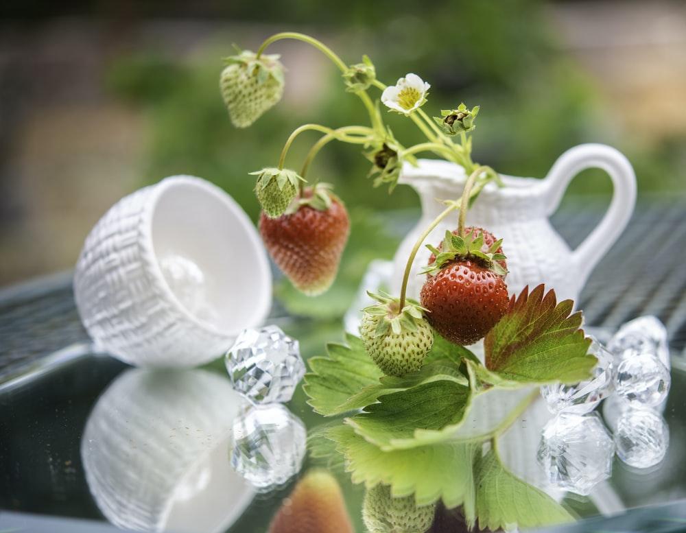 red strawberries on white ceramic mug