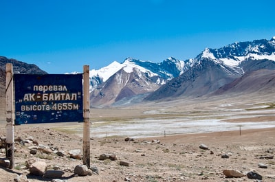 brown wooden signage near brown field and mountain during daytime tajikistan zoom background