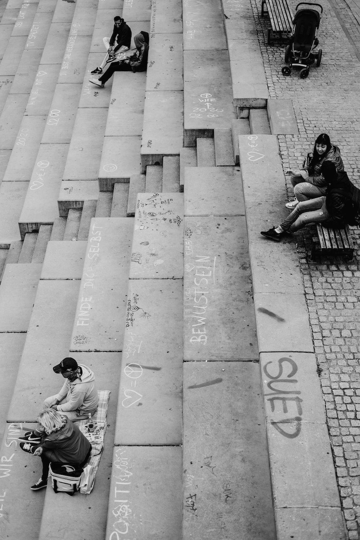 man in black jacket sitting on concrete pavement