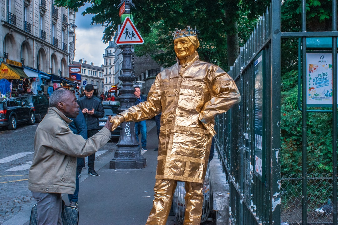 A French businessman shaking the hand of a statue performance artist.