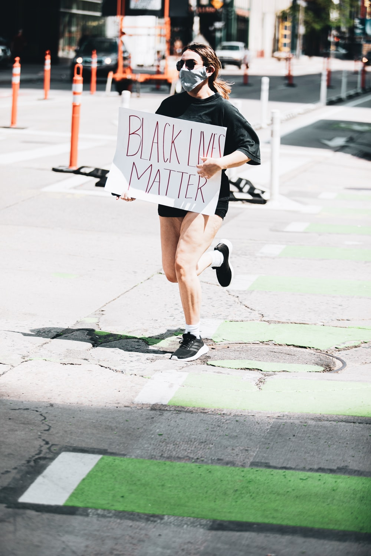 woman in black jacket and brown shorts walking on sidewalk during daytime