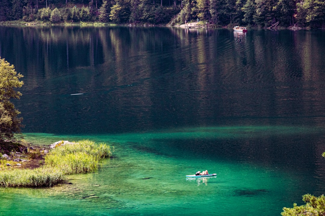 sunbathing on a paddle between the islands of lake Eibsee in crystal clear green water.