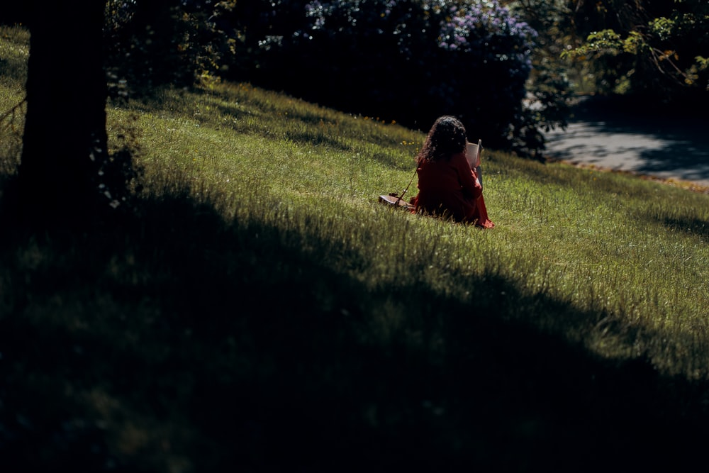 woman in red dress sitting on green grass field during daytime
