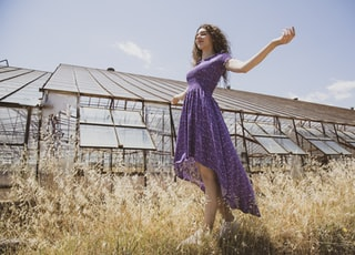 girl in purple dress standing on brown grass field during daytime