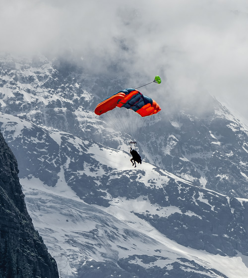 person in red and black jacket doing sky diving