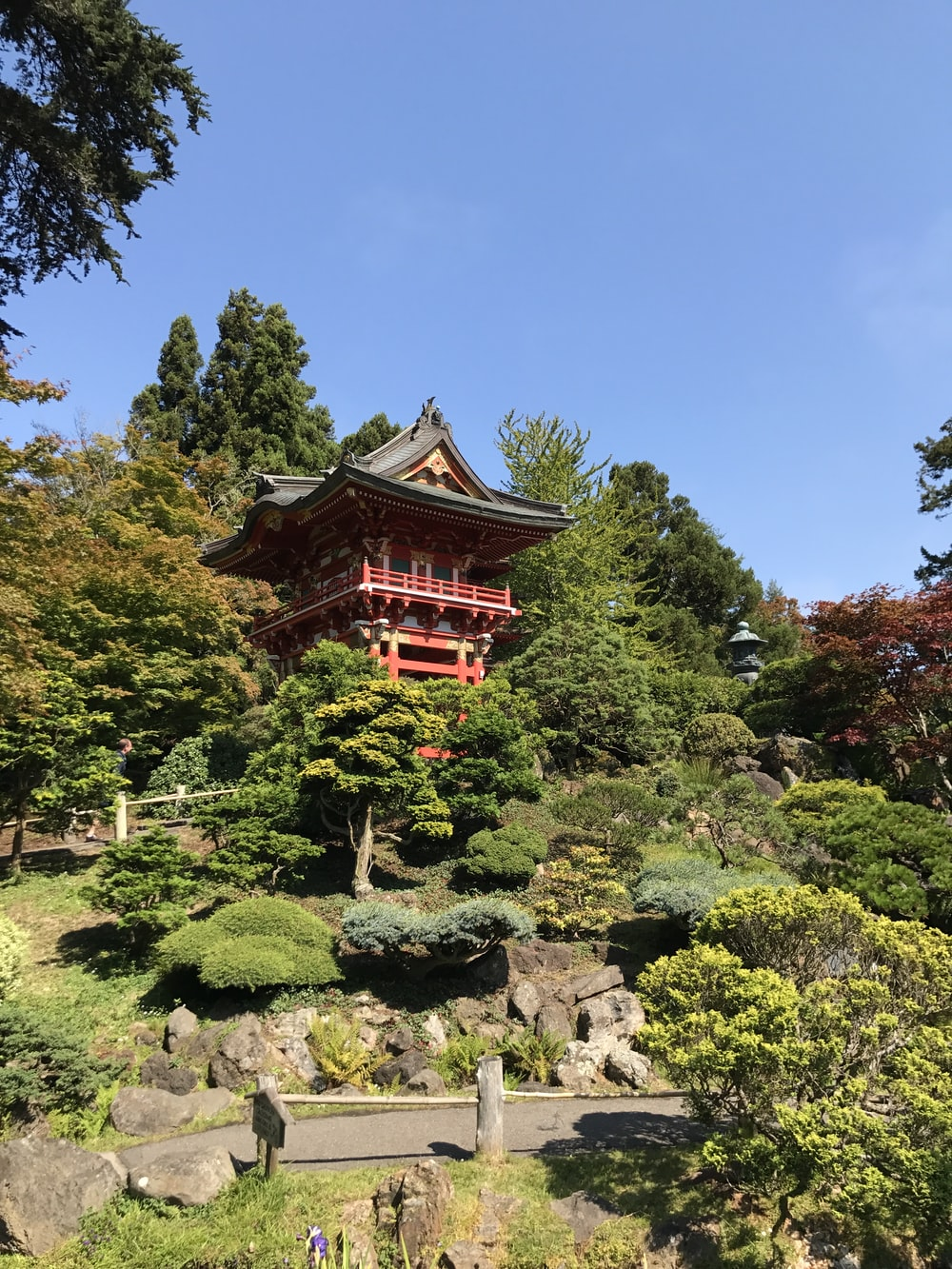 red and black pagoda temple surrounded by green trees under blue sky during daytime