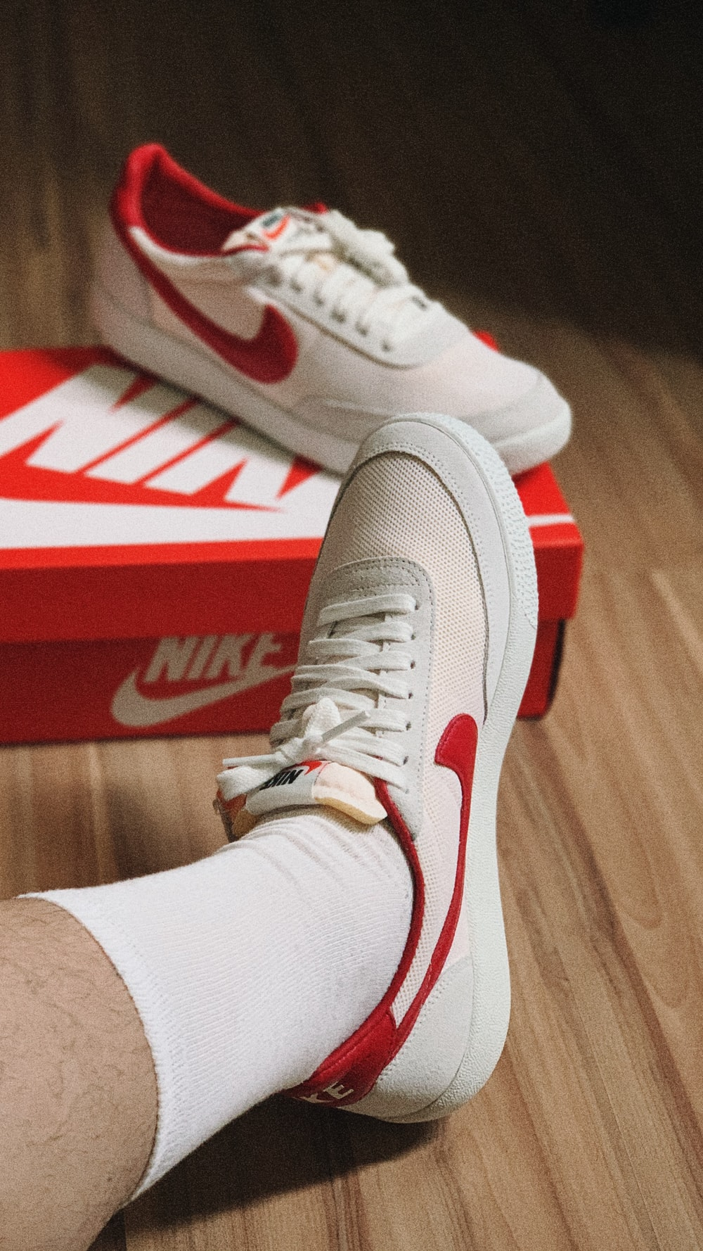 person wearing white and red nike athletic shoes
