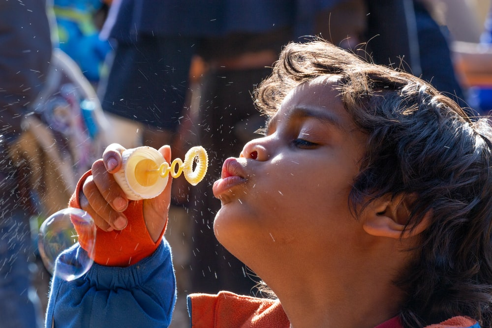 girl in red and blue shirt blowing bubbles