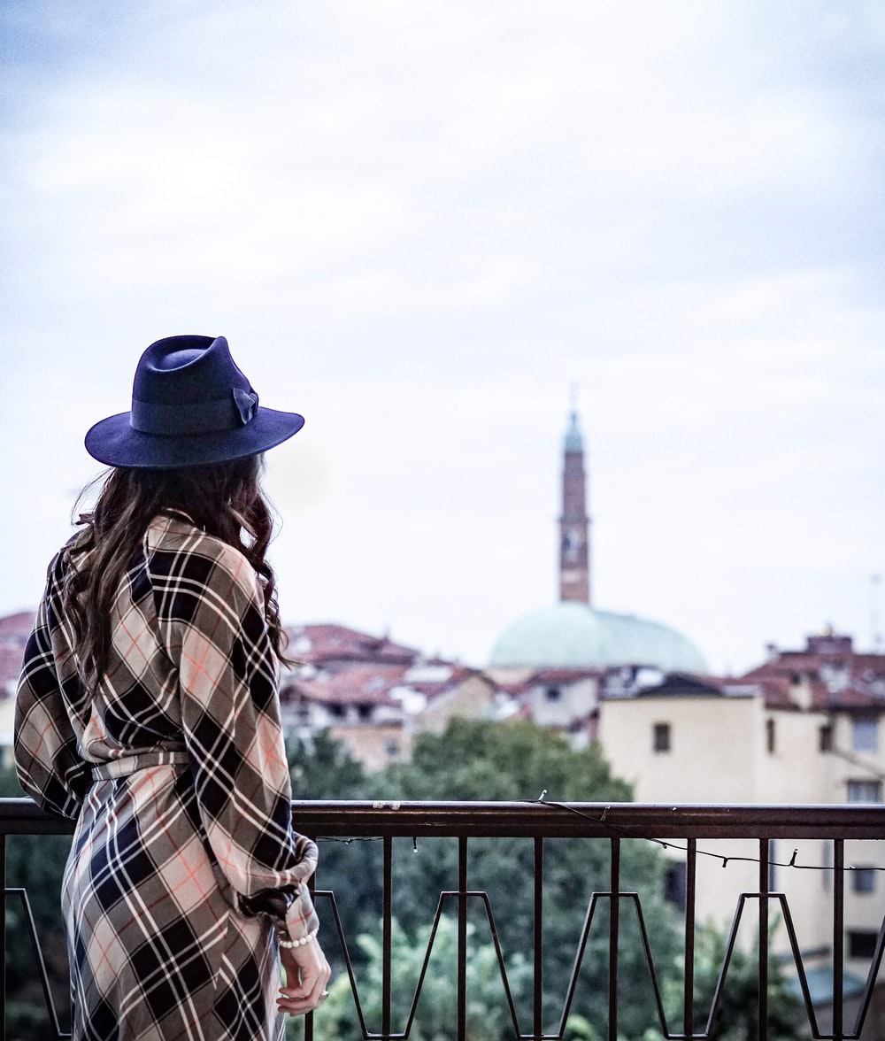 man in brown white and black plaid dress shirt and blue fedora hat standing near railings