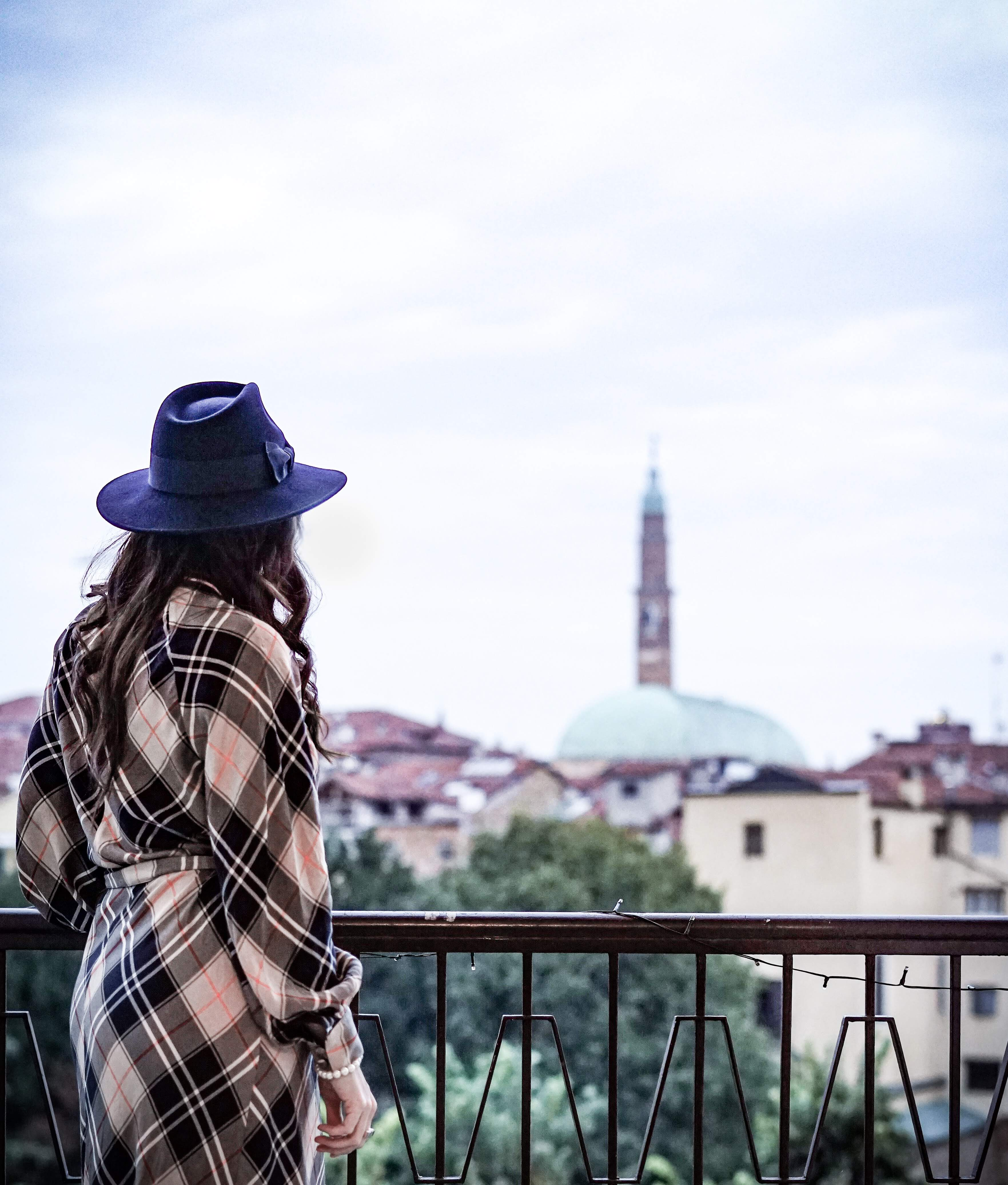 A woman with a hat admiring the view of the city.