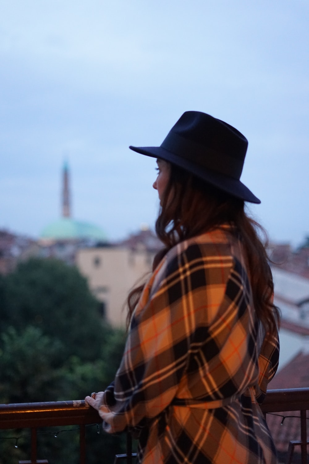 woman in black cowboy hat standing near green trees during daytime