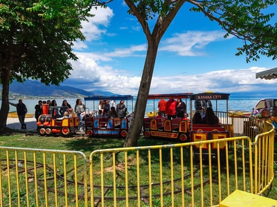 people riding on red and yellow roller coaster during daytime albania zoom background