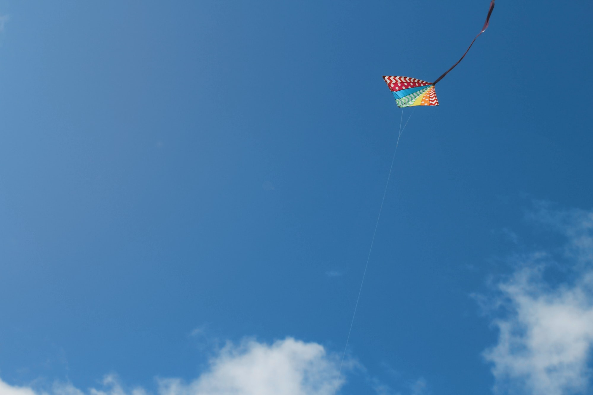 A colorful kite in a peaceful blue sky