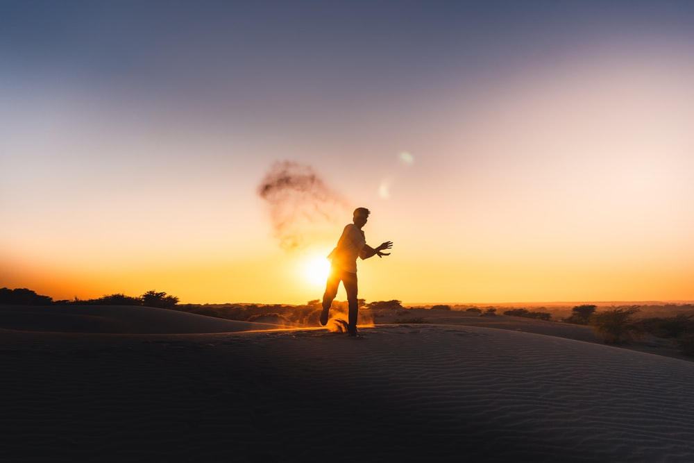 silhouette of man running on sand during sunset