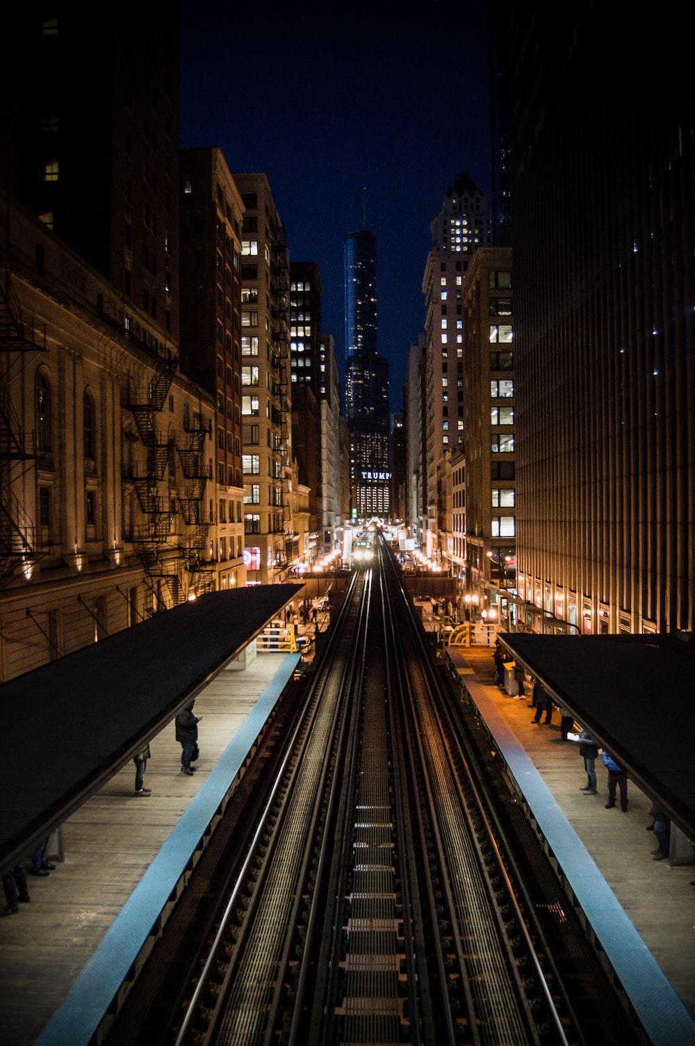 black metal train rail in between high rise buildings during night time
