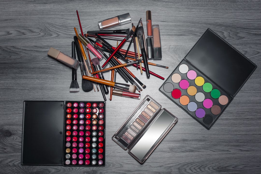 top view set of colored professional make up cosmetics with powder, pen, brush, tonal cream, concealer and palette; flat lay