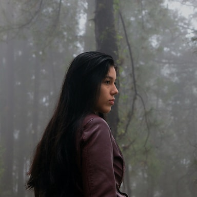 woman in brown jacket standing near trees during daytime