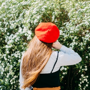 woman in white long sleeve shirt and red hat standing near white flowers during daytime