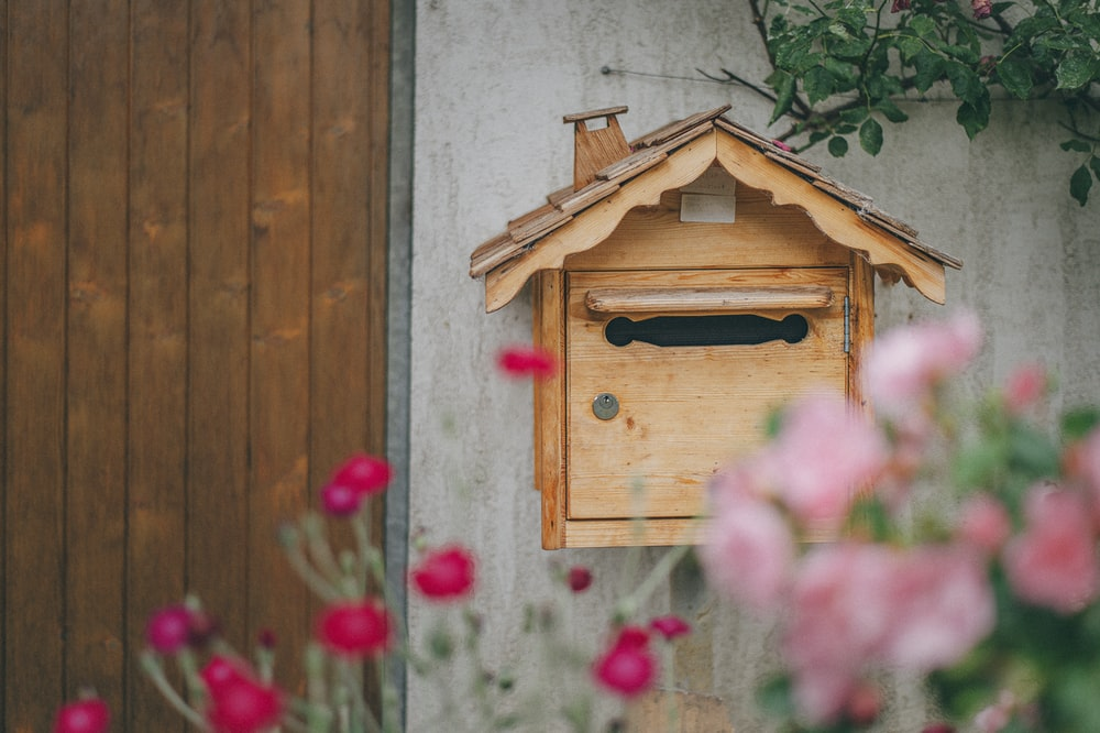 brown wooden birdhouse on gray wooden wall
