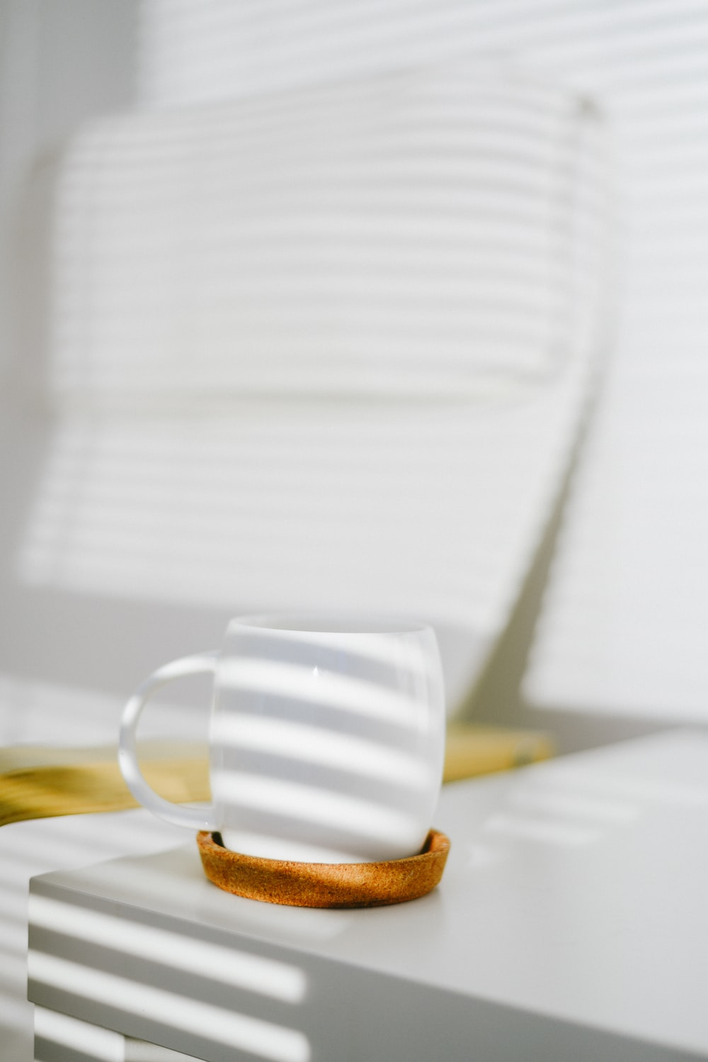 white ceramic mug with brown and white pastry on white ceramic plate