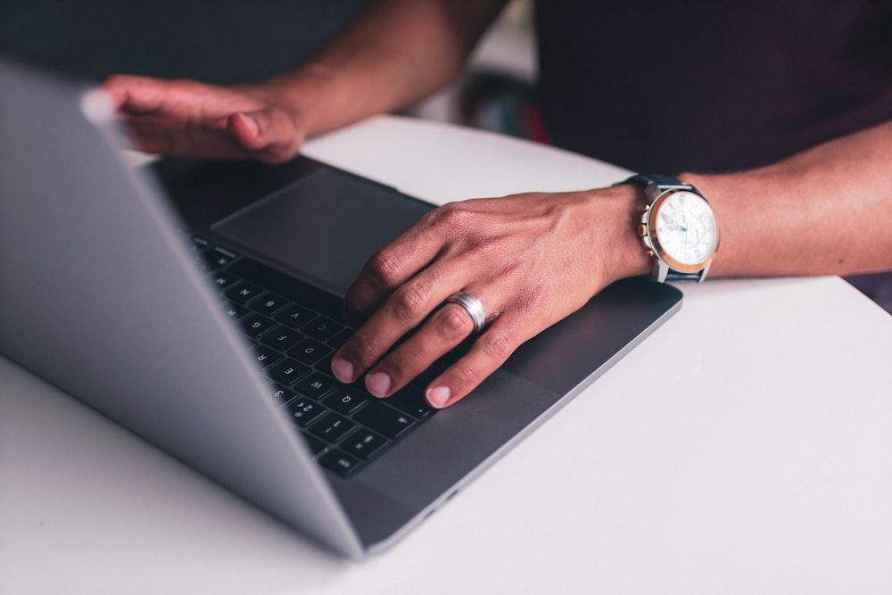 person wearing gold analog watch using black laptop computer