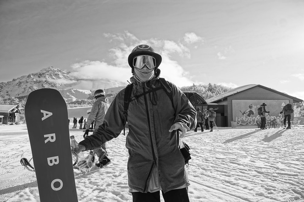 man in black jacket and pants holding snowboard
