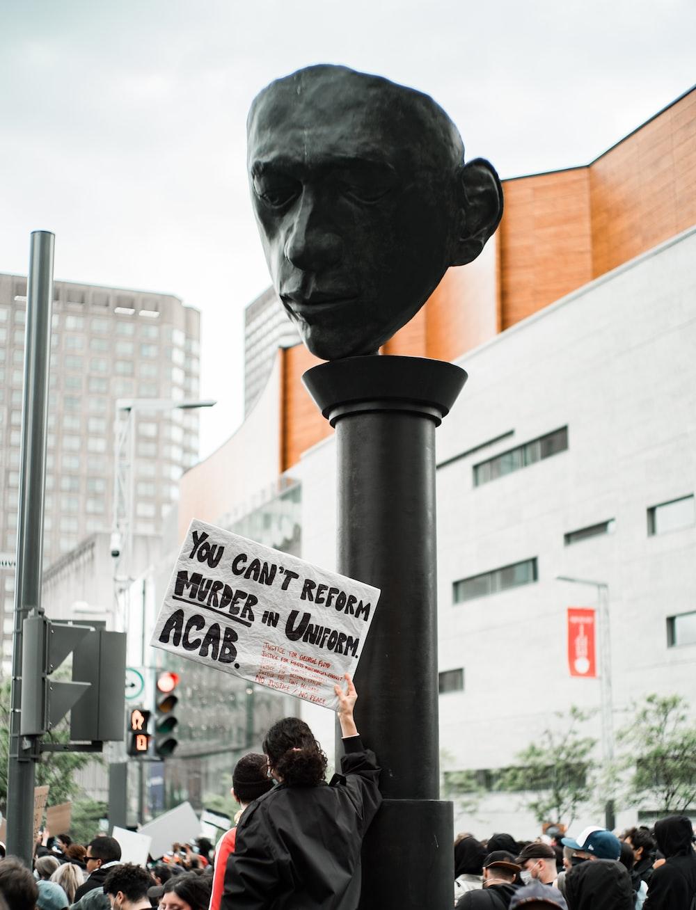 man in black jacket standing near black statue