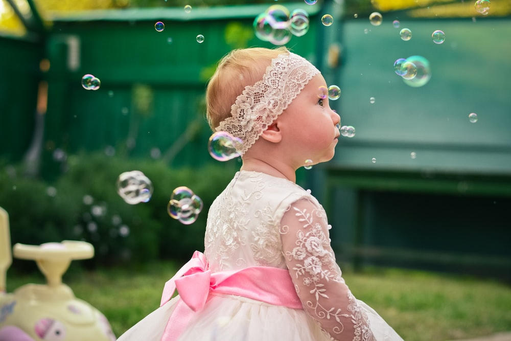 girl in pink dress blowing bubbles