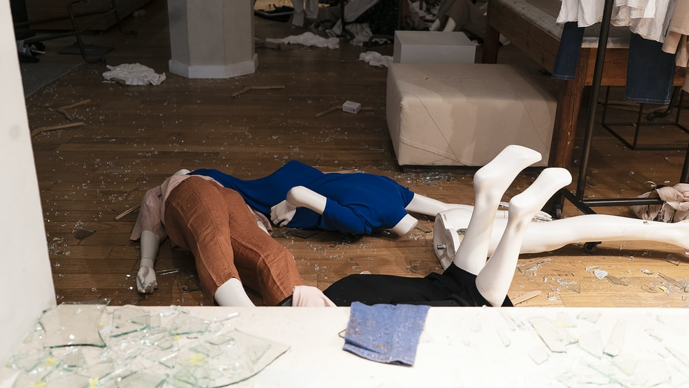 woman in blue shirt and brown pants lying on floor