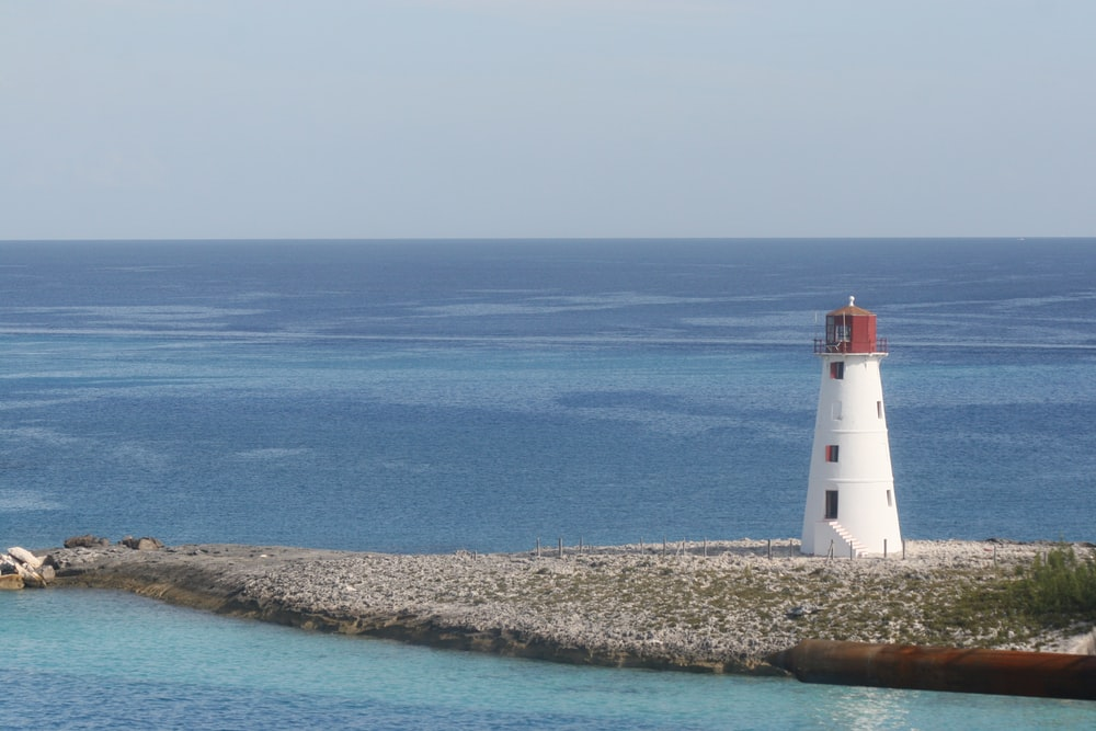white and red lighthouse near blue sea during daytime