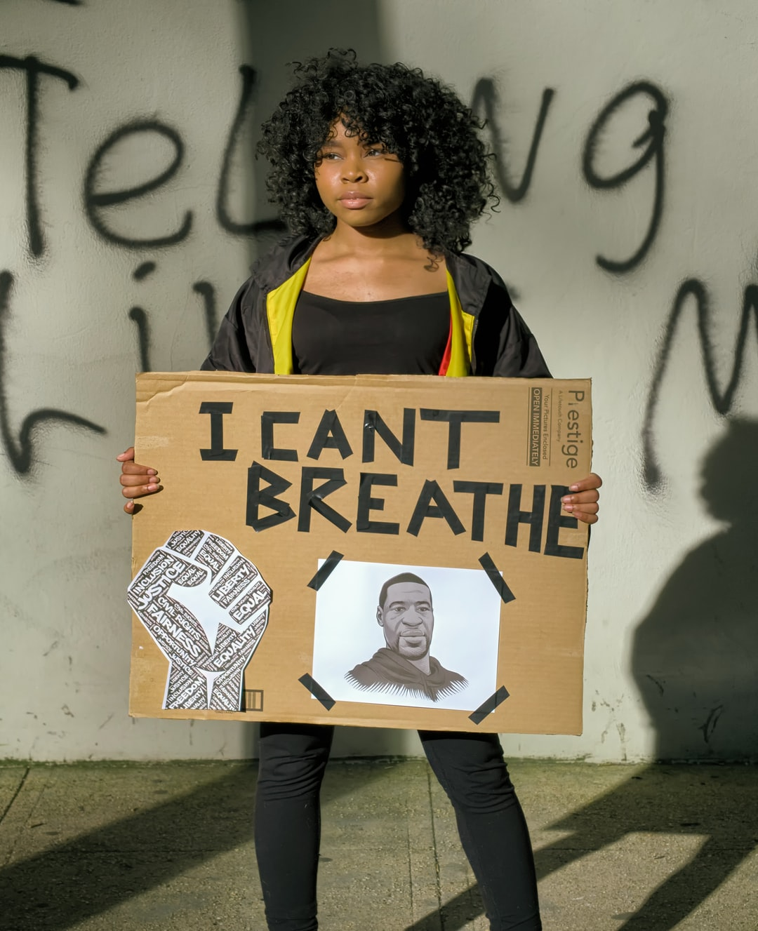 A protester in Washington DC holds a sign featuring George Floyd.