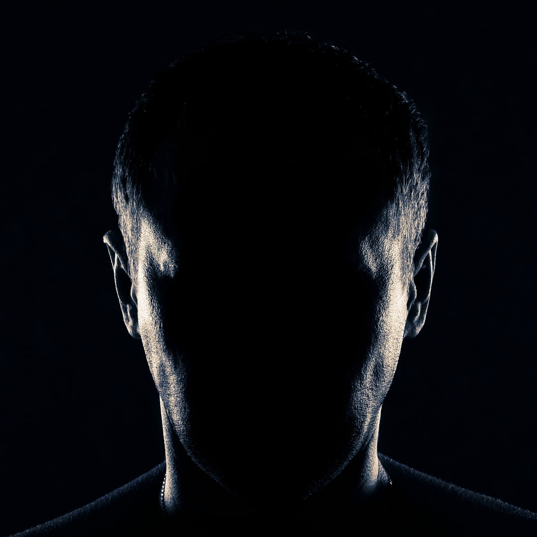 Anonymous. A man's portrait of an unknown man. You can't see the face. Black background. A man's head, a face beyond recognition is hidden by a shadow. The visible part of the right and left side of the face. Black-and-white photo. Help: paypal.me/63ru78