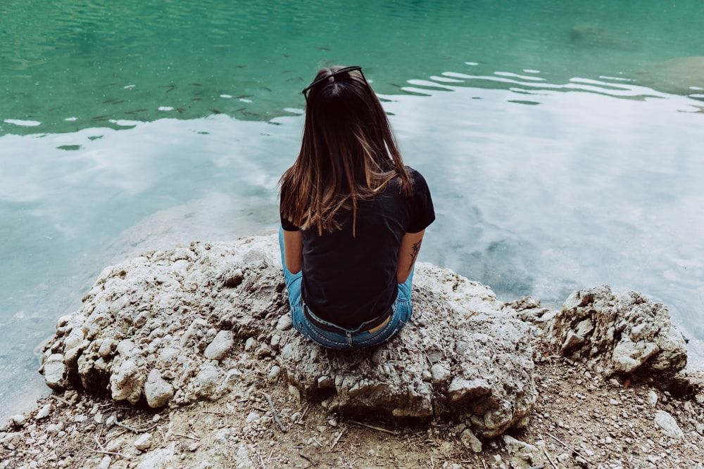 woman in blue shirt and blue denim shorts sitting on rock by the sea during daytime
