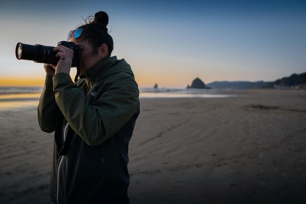 man in gray hoodie taking photo of sea during daytime