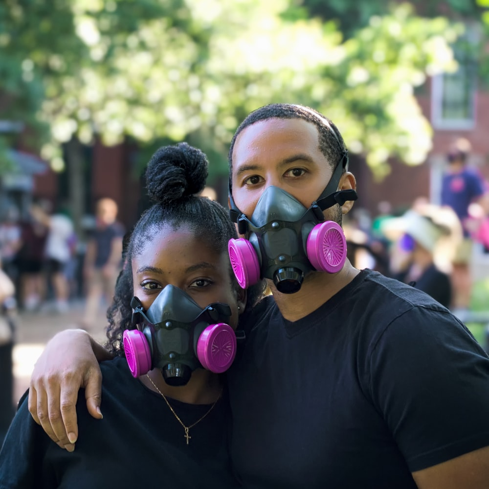 man in black crew neck t-shirt wearing purple and green gas mask