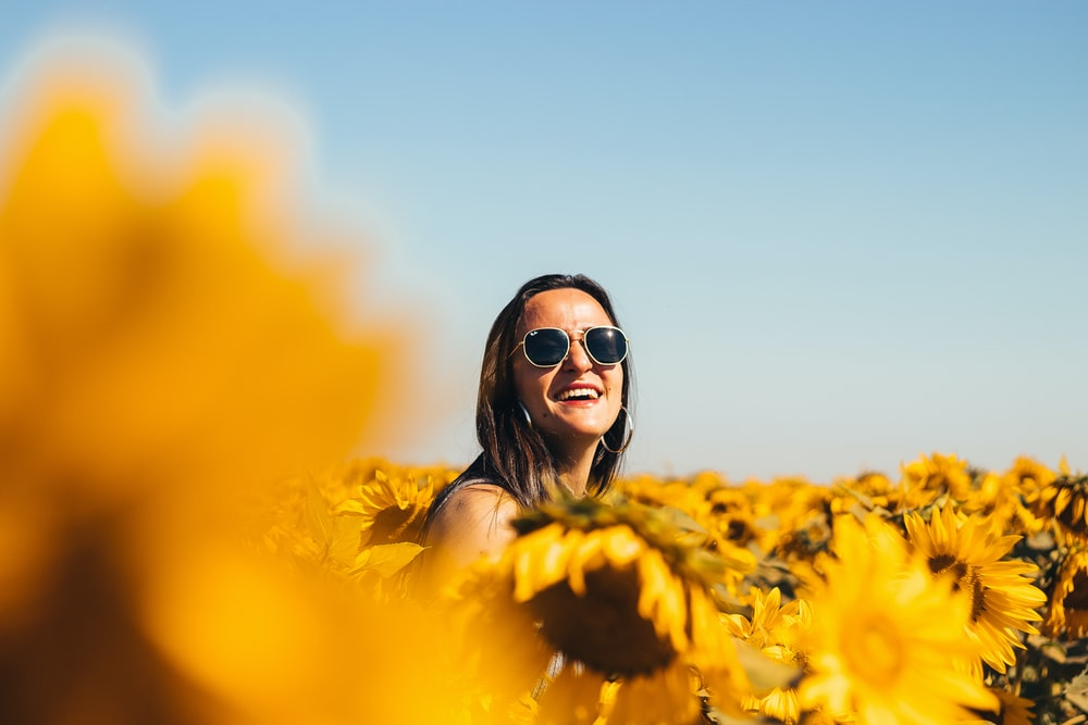 woman in black sunglasses on yellow flower field during daytime