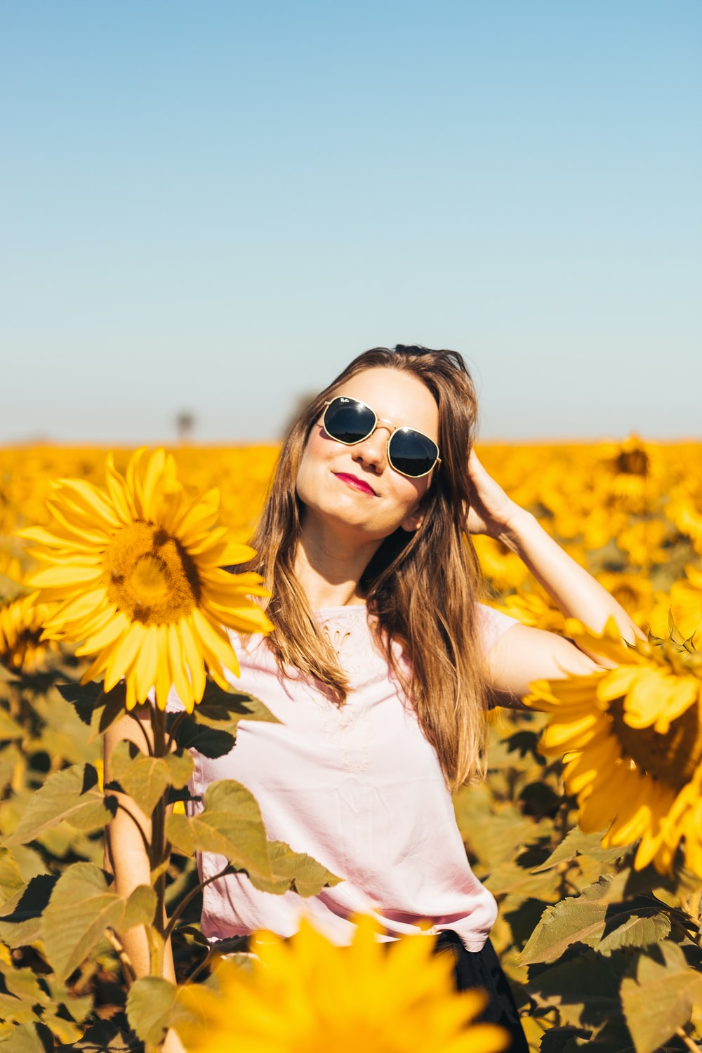 woman in white shirt standing on sunflower field during daytime