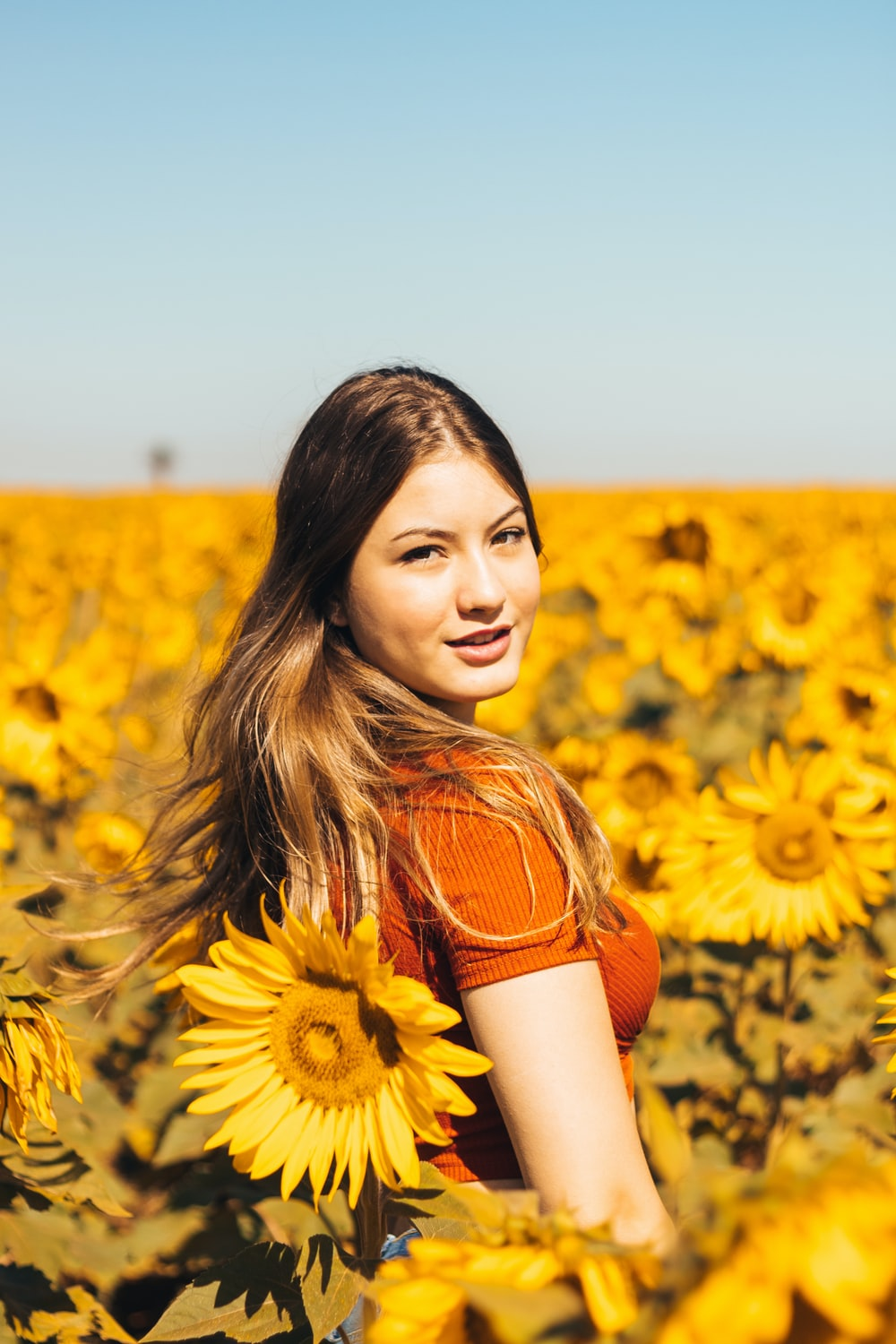 woman in orange and white stripe shirt standing on sunflower field during daytime