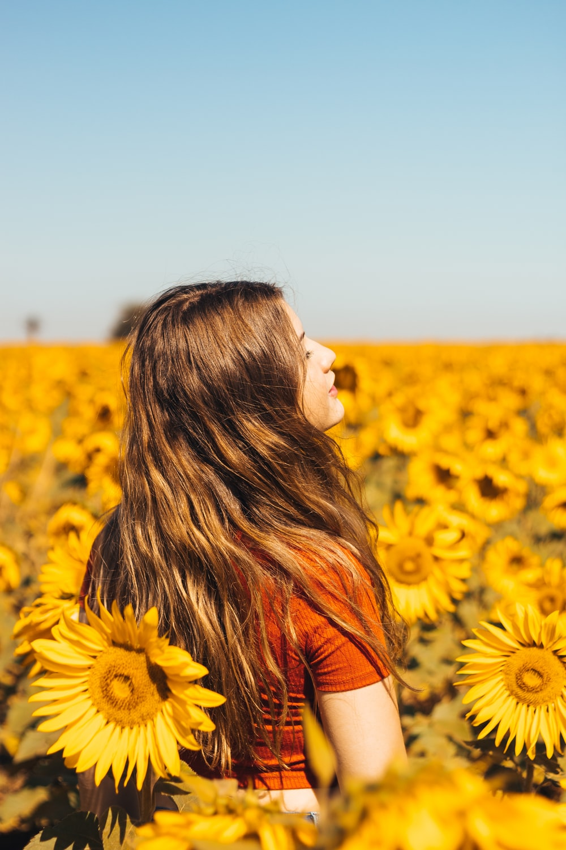 woman in orange shirt standing on sunflower field during daytime